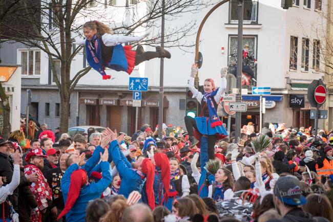 Heinzelmänncher Tänzerin im Dienstags Karnevalszug vor dem goldenen Kappes, werfen ihre Tanzmarie in die Luft
