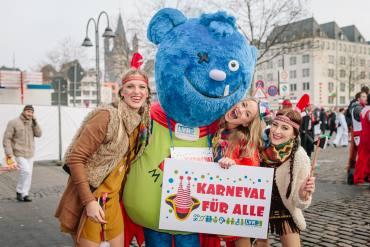 Karneval für alle ist das Motto des LVR . Drei Mädels feiern zusammen mit dem Maskottchen