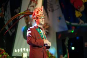 Der Bauer steht auf der Bühne und Trägt den festlichen Hut mit den Federn
