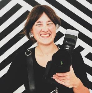 Wera Drewke vor schwarzweißem Hintergrund mit Kamera in der Hand