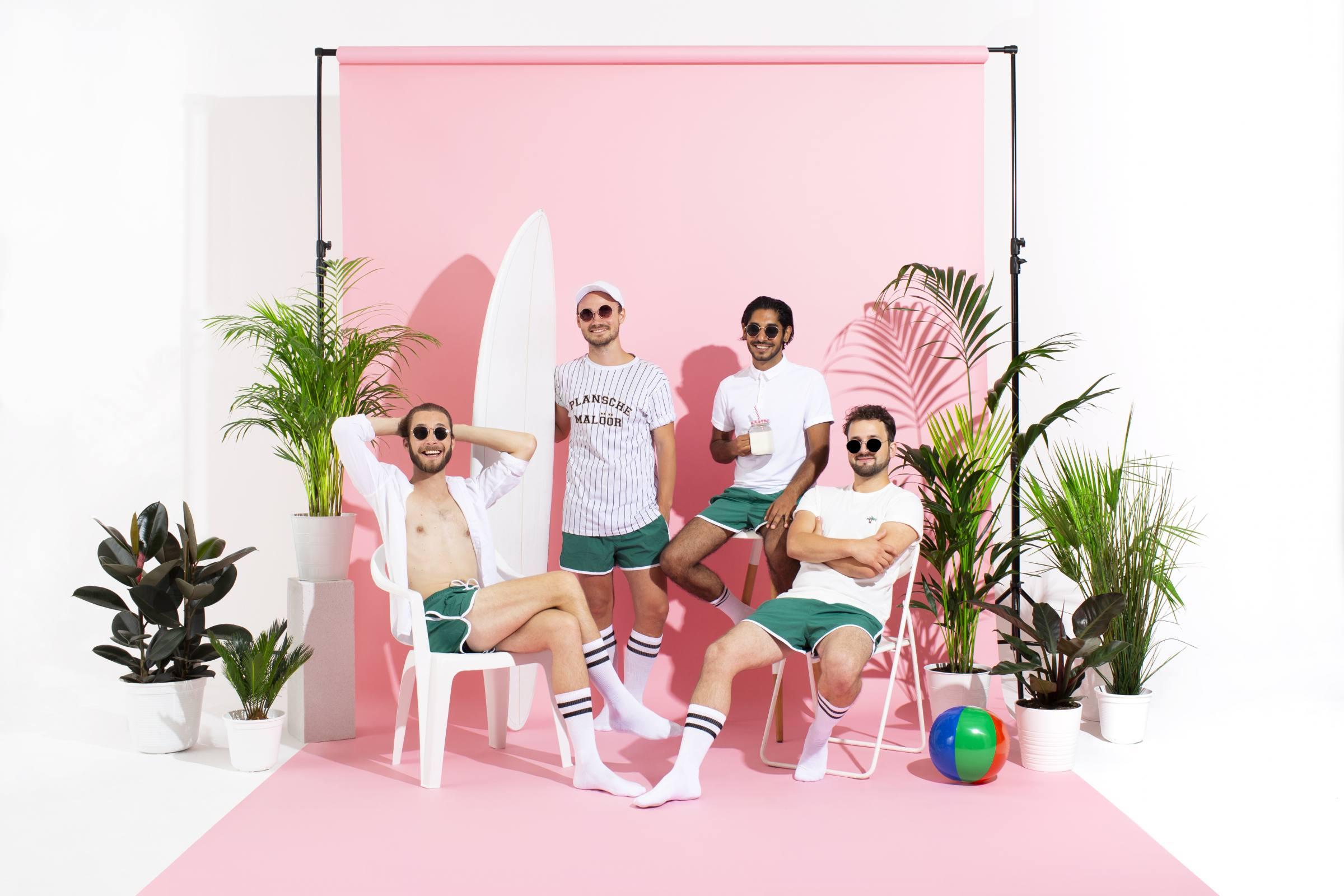Werbebild von Planschemalöör: die Band posiert vor einer rosa wand und sonnt sich im Scheinwerferlicht